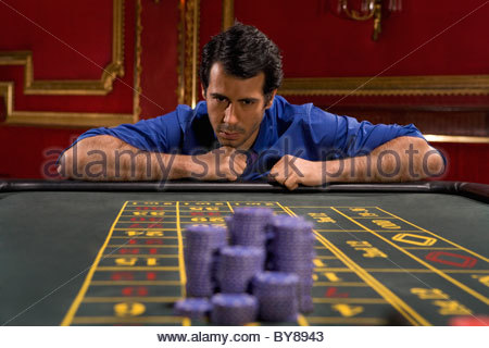 Anxious man looking bet on gaming table - Stock Photo
