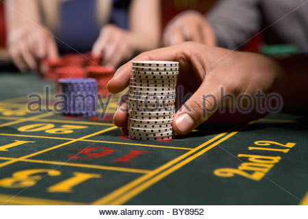 Man placing bet with gambling chips - Stock Photo