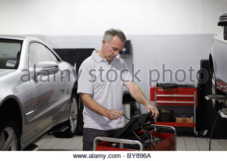 Mechanic working on computer in auto repair shop - Stock Photo