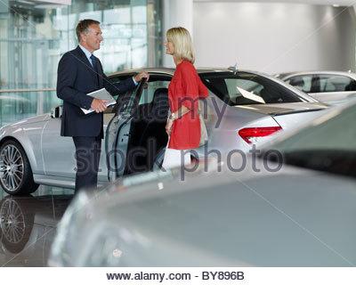 Salesman talking to woman in automobile showroom - Stock Photo