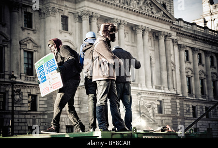 Students stand on top of a rubbish skip near parliament square during student protests against raised fees. London - Stock Photo