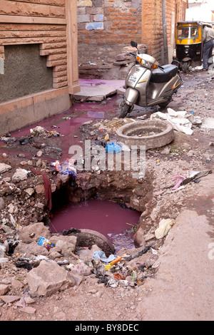 India, Rajasthan, Jodhpur, smashed man-hole cover in dilapidated street - Stock Photo