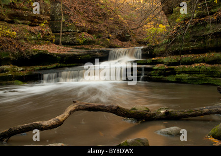 A waterfall roars over two small rock cliffs and into a pool of water produced by a time exposure leaving a silky - Stock Photo