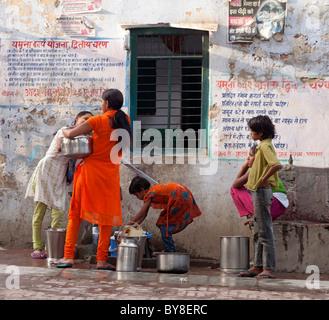 India, Uttar Pradesh, Agra, Teenage girls collecting water from village pump - Stock Photo