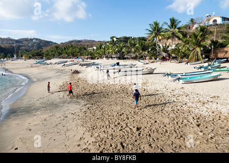 teenage Mexican boys play pick up soccer game on palm fringed beach with beached fishing boats Puerto Angel Oaxaca - Stock Photo