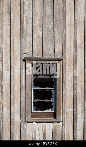 An old wooden building with a broken window, on the Mescalero American Indian reservation, New Mexico. - Stock Photo
