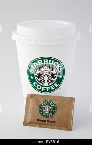 Starbucks single-use disposable paper takeaway coffee cup to go with plastic drink-through lid and one sachet of brown sugar. England UK