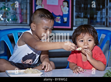 Humorous scene of a young boy attempting to feed his baby sister. Thailand S. E. Asia - Stock Photo