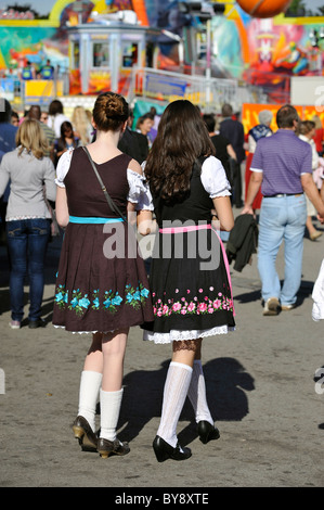 Two young women in Dirndl from behind at Oktoberfest, Munich, Germany - Stock Photo