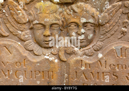 Two cherubs (one eyes open, one eyes shut) on a gravestone in the churchyard at Awre, Gloucestershire - Stock Photo
