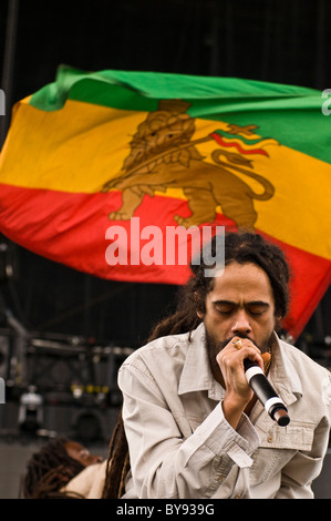 Damien Marley singing with a Rasta flag flying live in concert with Nas at Mile High Music Festival 2010. - Stock Photo