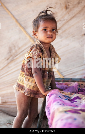 Poor lower caste Indian baby street girl in her tented home. Andhra Pradesh, India.  Selective focus - Stock Photo