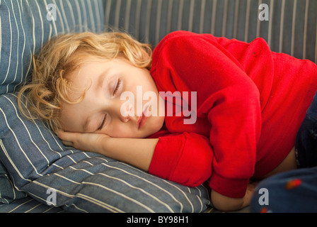 Sleeping child - Little girl child asleep on a sofa - Stock Photo