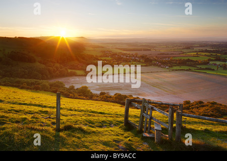 Stile with views across the West Sussex countryside. The evening sun making its descent behind the undulating Hillside. - Stock Photo