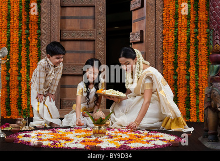 South Indian woman making a flower rangoli with son and daughter - Stock Photo