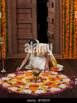 South Indian woman making a flower rangoli - Stock Photo