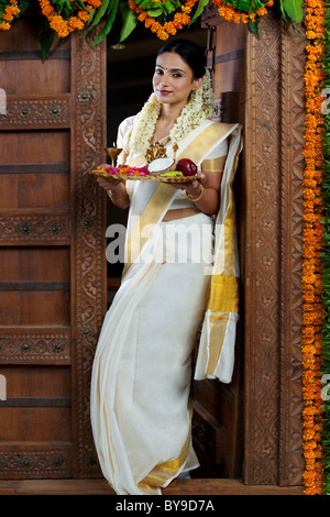 Portrait of a South Indian woman holding a tray - Stock Photo