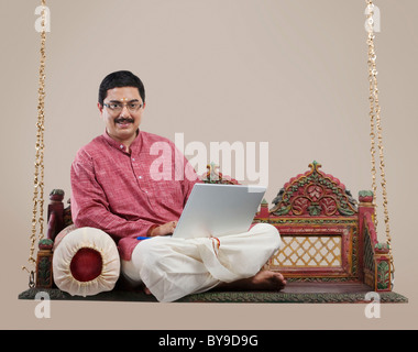 South Indian man with a laptop - Stock Photo
