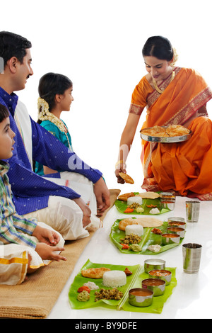 South Indian woman serving food to her family - Stock Photo
