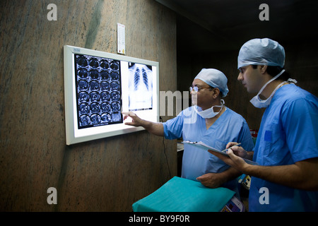 Surgeons looking at a CT scan - Stock Photo