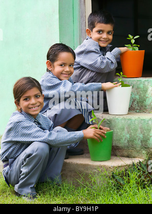 School kids with colored potted plants - Stock Photo