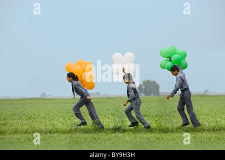 School students holding colored balloons - Stock Photo