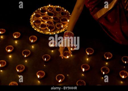 Woman arranging diyas - Stock Photo