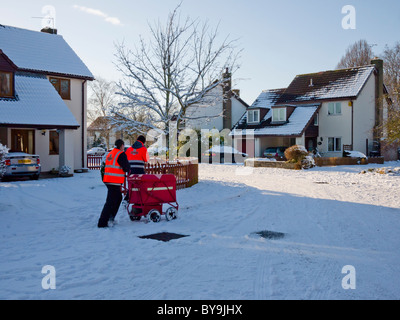 Two postmen in the street delivering mail to houses. Wrington, North Somerset, England. - Stock Photo
