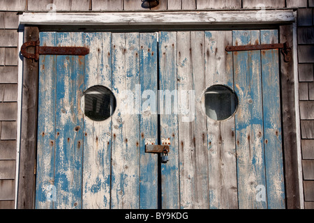Weathered doors of an old, rustic, cedar shingled house on Cape Cod, Massachusetts. - Stock Photo