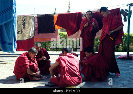 Buddhist monks and novices relax over a board game among laundry lines beside the great Rumtek monastery in Sikkim - Stock Photo
