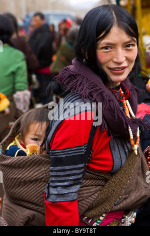 Tibetan woman with child in papoose on her back Norbulingka or Jewel Park, Tagten Migyur Podrang, Lhasa, Tibet, - Stock Photo