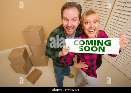 Goofy Couple Holding Coming Soon Sign in Room with Packed Cardboard Boxes.