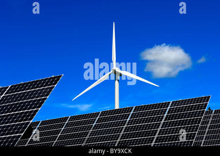 Solar panels of solar power farm in front of a wind turbine, Photovoltaics centre Mont Soleil, Switzerland - Stock Photo