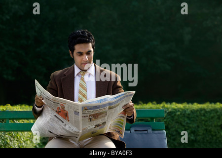 Businessman reading a newspaper in a park - Stock Photo