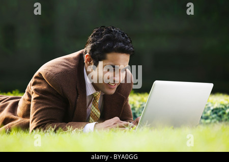 Businessman with a laptop in a park - Stock Photo