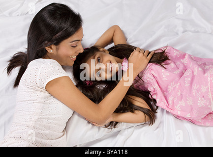 Mother and daughter lying together in bed - Stock Photo