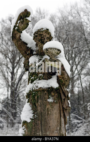 Snow-covered baroque statue of a woman pouring from a jug, Kalkum moated castle, Duesseldorf, Lower Rhine region - Stock Photo