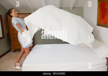 Hotel maid putting throwing sheet on bed - Stock Photo