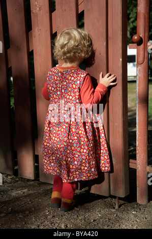 Four year old girl standing at a fence - Stock Photo