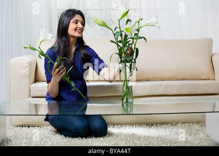 Young woman arranging flowers in a vase - Stock Photo