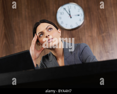 Business woman sitting at desk thinking - Stock Photo
