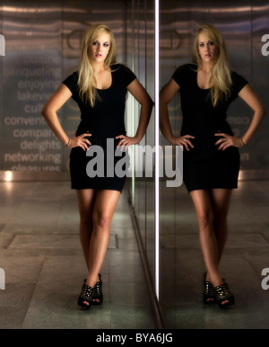 Young woman with long blonde hair wearing a black dress posing in front of glass wall, reflection, mirror image - Stock Photo