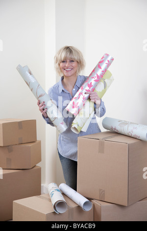 Woman holding wallpaper samples - Stock Photo