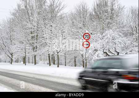 Car on a snow-covered road in winter, slip hazard, warning sign, prohibition sign, blur - Stock Photo