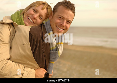 Woman embracing man from behind on beach - Stock Photo