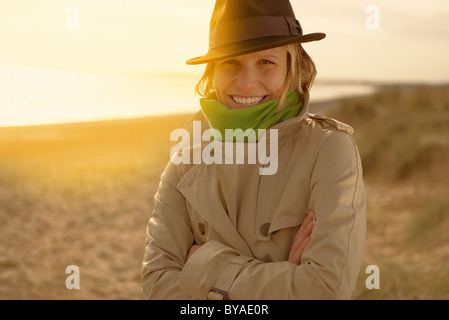Young woman on beach in hat and raincoat - Stock Photo