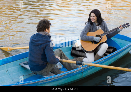 Girl playing guitar in row boat - Stock Photo