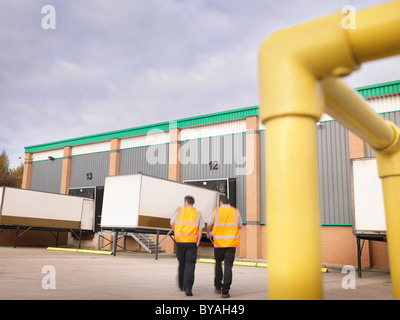 Workers with containers in loading bay - Stock Photo
