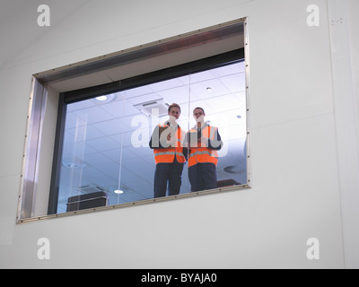 Engineers look out of window in hangar - Stock Photo