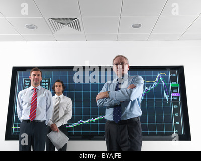 Businessmen in front of graphs on screen - Stock Photo